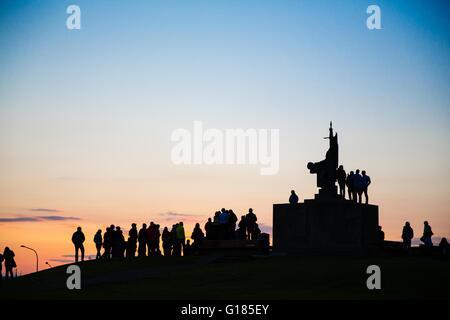 Silhouette della folla di persone intorno a un monumento al tramonto, Reykjavik, Islanda Immagini Stock