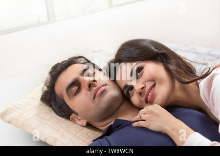 Coppia giovane rilassante sul letto Immagini Stock