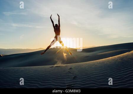 Nudo di donna nel deserto a braccia alzate saltando a metà in aria Immagini Stock