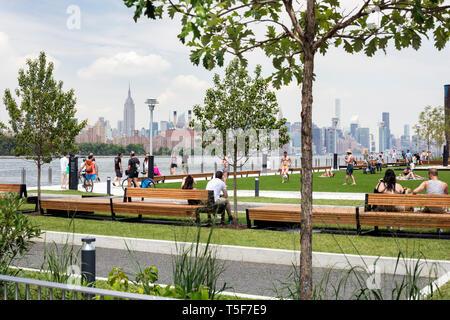 Campo da bocce e campo di flex con East River e Manhattan in background. Domino Park, Brooklyn, Stati Uniti. Architetto: James Corner Field operat Immagini Stock