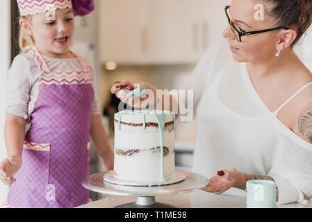 Madre e figlia decorare la torta Immagini Stock