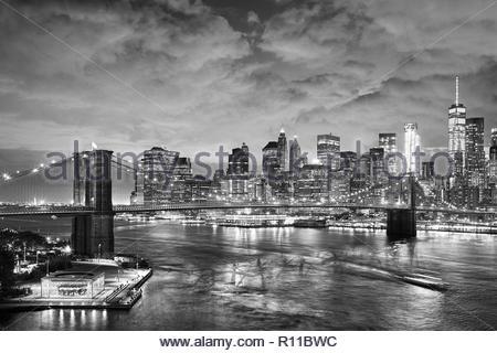 In bianco e nero girato di edifici e di un ponte sul fiume nella città Immagini Stock