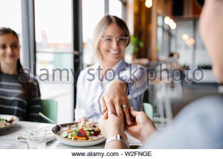 Felice giovane donna che mostra anello di fidanzamento di amici nel ristorante Immagini Stock
