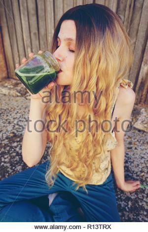 Una donna con capelli lunghi bere un frullato verde Immagini Stock