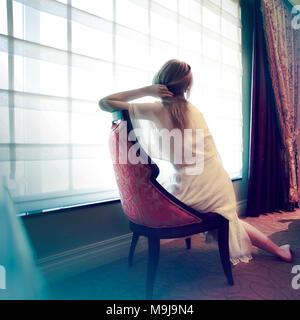 Donna seduta in una stanza Immagini Stock