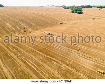 Antenna della pressa del trattore rendendo le balle di paglia nel campo dopo la mietitura del grano in estate in agriturismo Immagini Stock
