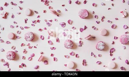 Flat-lay di rosa dolci macaron cookies, lilla marshmallows e petali di rosa pastello su sfondo rosa, vista dall'alto. Food texture, sfondo e wallpap Immagini Stock