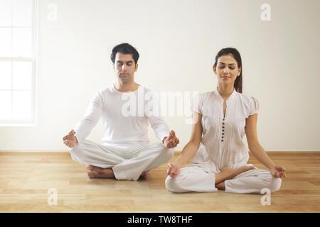 Coppia giovane di eseguire lo yoga Immagini Stock