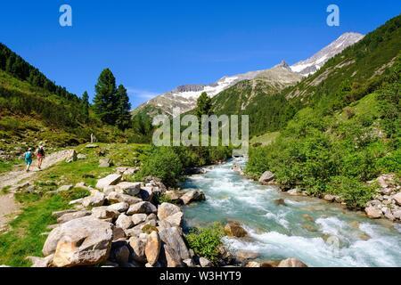 Gli escursionisti a Zamserbach, Zamser Grund, Ameiskopf e Schrammacher, Alpi della Zillertal, Zillertal, Tirolo, Austria Immagini Stock