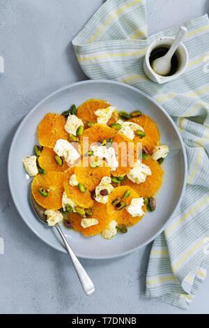 Arancione, bocconcini e pistacchio insalata con una brocca di condimento piccante. Immagini Stock