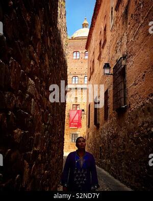 Una donna entra in una stretta strada di fronte al palazzo Toledo-Moctezuma's tower nella città medievale di Caceres, Estremadura, Spagna Immagini Stock
