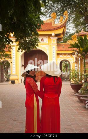 Le ragazze che indossano Ao Dai abito, Tran Quoc Pagoda, West Lake (Ho Tay), Hanoi, Vietnam (MR) Immagini Stock