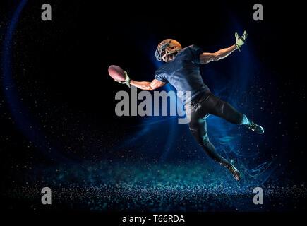 Giocatore di football di raggiungere per la cattura di calcio Immagini Stock