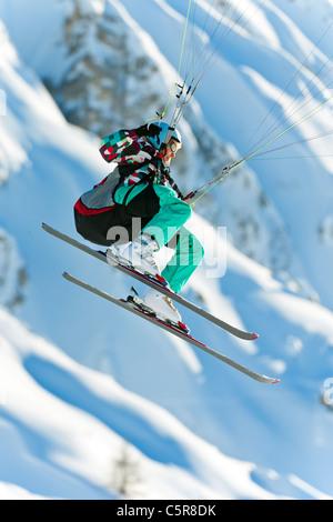 Un pilota di parapendio battenti la sua ala passato montagne innevate. Immagini Stock