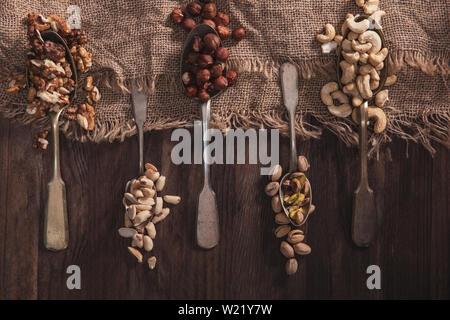 Diversi tipi di dadi sul vecchio cucchiai e composizioni fatte di legno vecchio e il materiale Immagini Stock