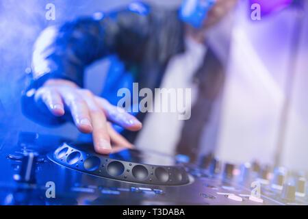 Il mixaggio DJ al party festival con la luce blu e fumo in background - Estate vista notturna della discoteca all'interno. La messa a fuoco a portata di mano Immagini Stock
