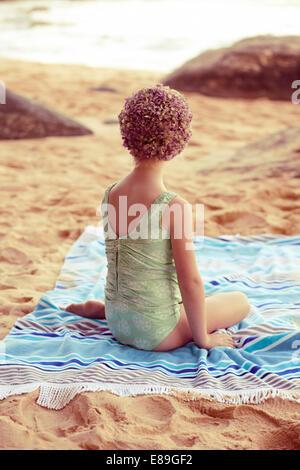 La ragazza di swimcap seduto sulla spiaggia coperta Immagini Stock