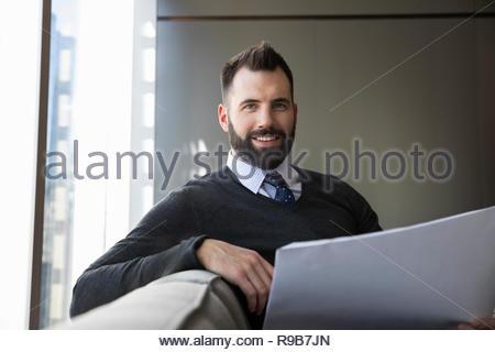 Ritratto fiducioso e sorridente architetto maschio rivedendo blueprints Immagini Stock