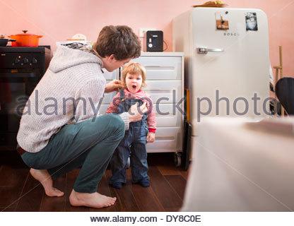 Giovane padre vestire il suo bambino stanco di mattina Immagini Stock