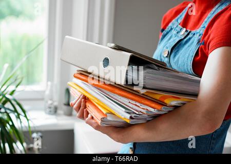 Femmina giovane studente di college che trasportano pila di libri e di legante Immagini Stock