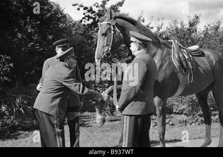 Unione Sovietica il maresciallo Semyon Budenny saluta il suo cavallo a dacha in Podmoskoviye Immagini Stock