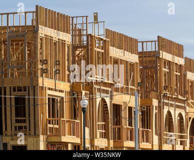 Un edificio di appartamenti in costruzione sulla giornata di sole sul cielo blu sullo sfondo Immagini Stock