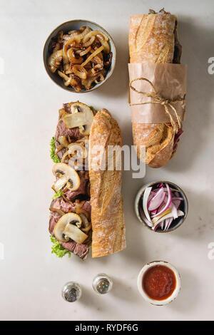 Aperto e legato carni bovine baguette con funghi champignon, insalata verde, cipolla fritti con ingredienti di bocce su marmo bianco dello sfondo. Fla Immagini Stock