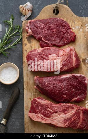 Materie black angus ottima bistecca di manzo varietà su vintage tagliere con rosmarino, sale marino e spezie Immagini Stock
