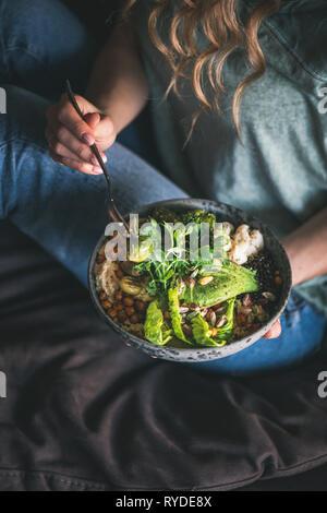 Una sana la cena o il pranzo. Curly donna in maglietta e jeans seduti e mangiare vegan superbowl Buddha o ciotola con hummus, verdure, insalate fresche, fagioli Immagini Stock