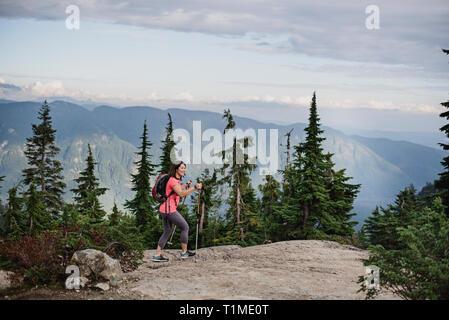 Donna escursionismo sulla cima, cane montagna, BC, Canada Immagini Stock