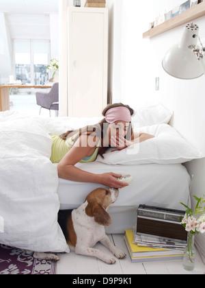 Bruna giovane donna giaceva a letto Immagini Stock