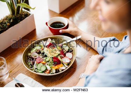 Donna di mangiare insalata in cafe Immagini Stock