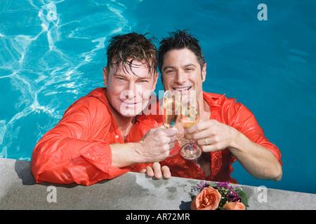 Completamente vestito coppia gay bevendo champagne in piscina Immagini Stock