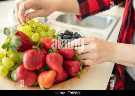 Donna mette uva verde, fragole e mirtilli nella ciotola di legno in cucina. Immagini Stock