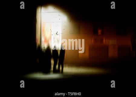 Un gruppo di persone in piedi la notte con una lanterna. Immagini Stock