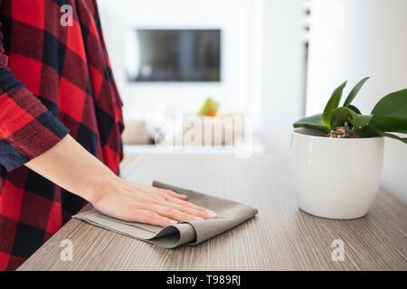 La donna pulisce la polvere utilizzando tessuto grigio dalla credenza in legno con impianto in salotto. Immagini Stock