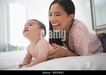 Riproduzione di madre con bambino figlio posa sul letto Immagini Stock