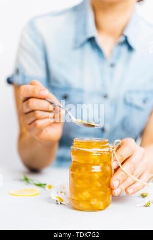 Donna con una maglietta blu tenendo un cucchiaio di succo di limone Marmellata da un vaso Immagini Stock
