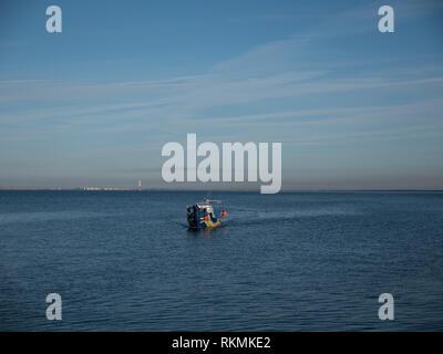 Imbarcazione a motore vela lontano sulle onde del mare Immagini Stock