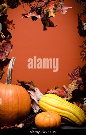 Autunno ortaggi, zucche e foglie su un sfondo di legno con sfondo arancione Immagini Stock