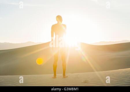 Nudo di donna nel deserto permanente sulla duna a luce solare Immagini Stock
