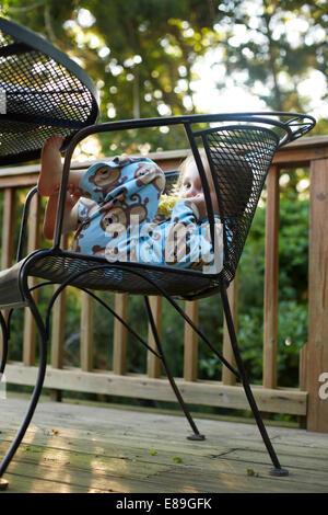 Bambino in appoggio su una sedia sul ponte Immagini Stock