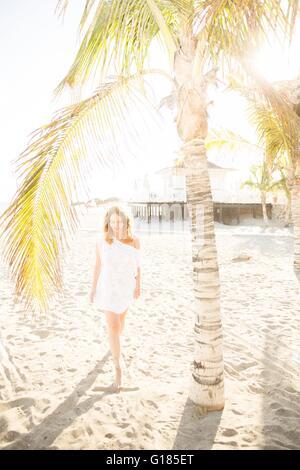 Lunghezza piena vista frontale di metà donna adulta sulla spiaggia sotto il palm tree, Tenerife, Isole Canarie, Immagini Stock