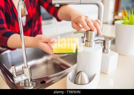 La donna è il dosaggio del sapone sulla spugna in cucina. Immagini Stock