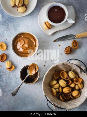 I cookie di noce in un cestello con dulce de leche in una ciotola e tazza da tè su sfondo grigio Immagini Stock