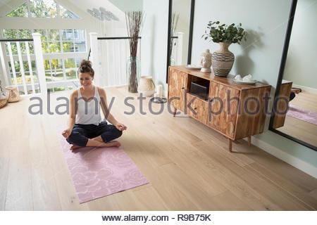 Donna felice a praticare yoga a casa Immagini Stock