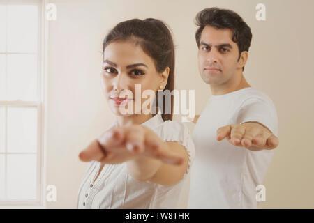 Coppia giovane fare esercizio di stretching mani Immagini Stock