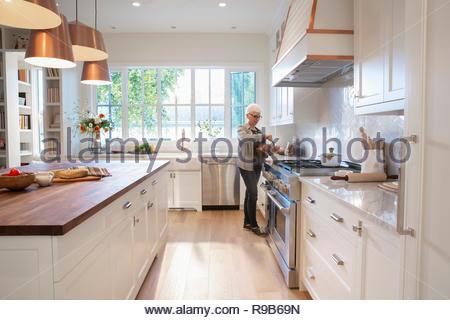 Senior donna preparando il tè in cucina Immagini Stock
