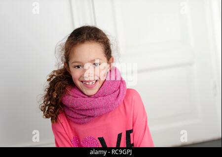 Ritratto di ragazza sorridente con sciarpa rosa Immagini Stock