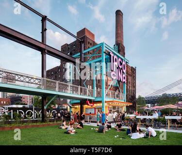Ristorante Tacocina contro lo sfondo del Domino ex fabbrica di zucchero. Domino Park, Brooklyn, Stati Uniti. Architetto: James angolo opera sul campo Immagini Stock